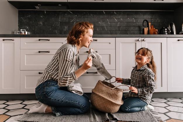 Rudowłosa kobieta żartuje córce i wyjmuje z koszyka brudne ubrania.