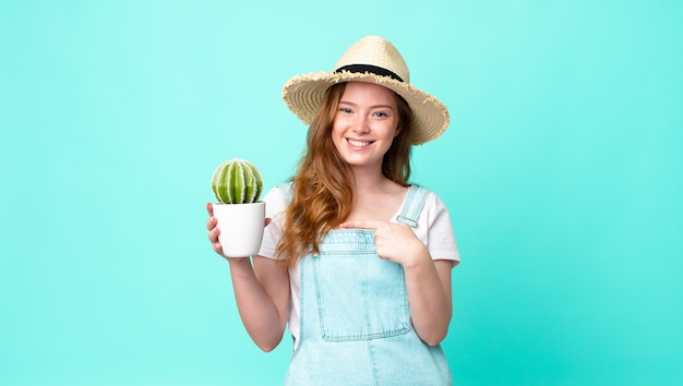 Rudowłosa ładna farmerka uśmiechnięta radośnie, czująca się szczęśliwa, wskazująca na bok i trzymająca kaktusa