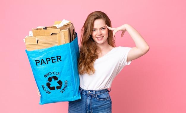 Rudowłosa ładna kobieta czuje się zdezorientowana i zdezorientowana, pokazując, że jesteś szalona i trzymasz papierową torbę z recyklingu