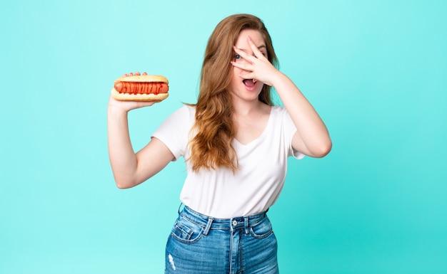 Rudowłosa ładna kobieta wygląda na zszokowaną, przestraszoną lub przerażoną, zakrywa twarz dłonią i trzyma hot doga