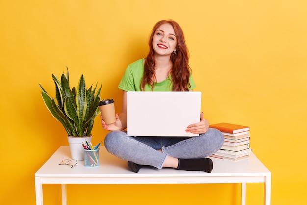 Rudowłosa ładna młoda dama patrząc z uśmiechem, trzymając notatnik siedząc na stole i używając laptopa, pije jednorazowy kubek gorącej herbaty, nosi zieloną koszulkę i dżinsy.