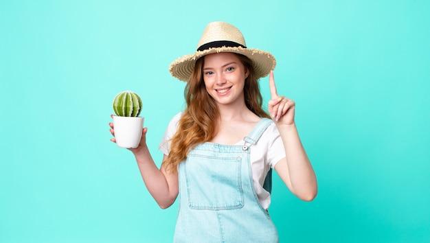 Rudowłosa ładna rolniczka uśmiechnięta i wyglądająca przyjaźnie, pokazująca numer jeden i trzymająca kaktusa