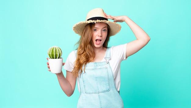 Rudowłosa ładna rolniczka wygląda na szczęśliwą, zdumioną i zdziwioną i trzyma kaktusa