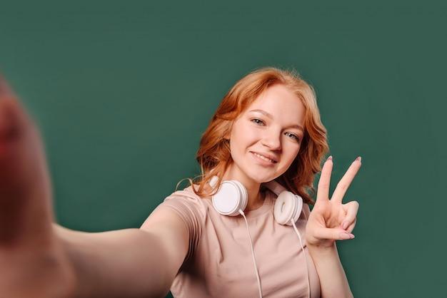 Rudowłosa młoda dziewczyna bierze selfie z perspektywy pierwszej osoby i pokazuje znak wiktoriański, stojąc na białym tle na zielonej ścianie z miejscem na tekst.