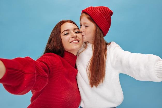 Rudowłosa młoda dziewczyna w kapeluszu całuje w policzek swoją starszą uśmiechniętą siostrę na niebieskiej ścianie