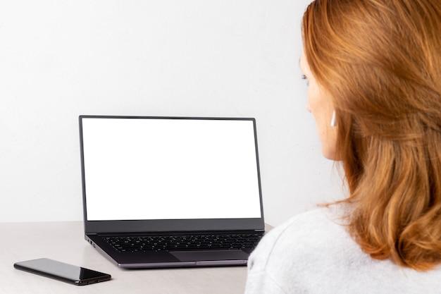 Rudowłosa młoda kobieta siedzi przed laptopem z białą makietą na ekranie