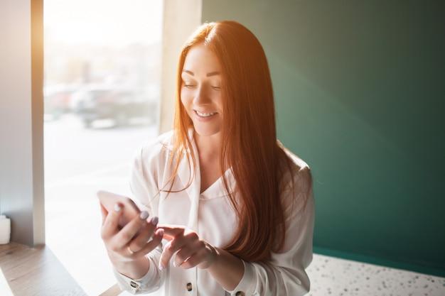 Rudowłosa młoda kobieta siedzi w kawiarni i trzyma telefon. modelka dotyka ekranu palcem wskazującym