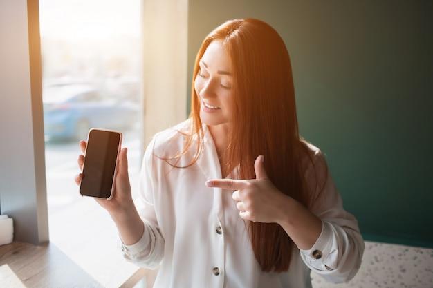Rudowłosa młoda kobieta siedzi w kawiarni i trzyma telefon. modelka wskazuje palcem wskazującym na smartfon.