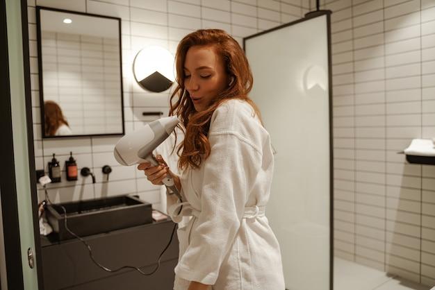 Rudowłosa młoda kobieta śpiewa pod prysznicem, śni z suszarką do włosów w dłoniach zamiast mikrofonu.