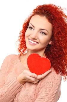 Rudowłosa młoda kobieta trzyma serce, na białym tle