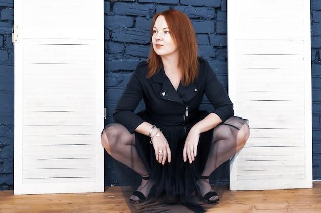 Rudowłosa młoda kobieta w niebieskiej sukience siedzi na jego zadzie. wulgarna pozycja, flirtująca, przyciągająca uwagę