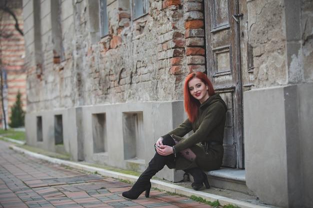 Rudowłosa młoda kobieta w pięknej zimowej sukience siedząca przy wejściu do starego budynku