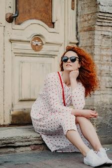 Rudowłosa myśląca kobieta odpoczywa po spacerze, pozuje przy starym budynku