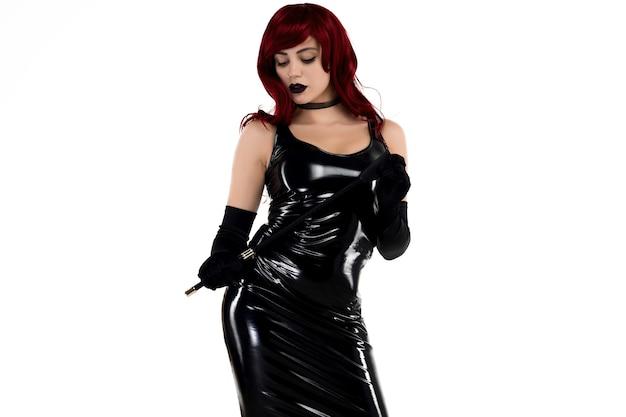 Rudowłosa namiętna dama w czarnej lateksowej sukience z biczem w dłoniach na białym tle