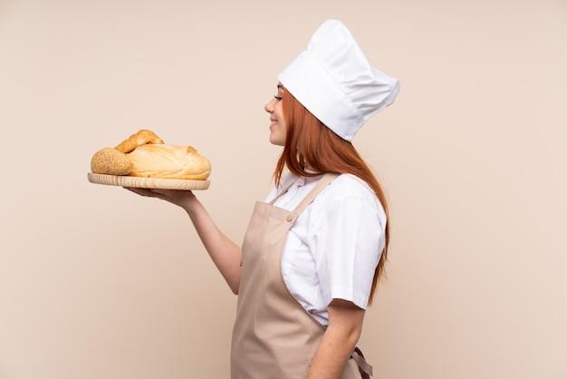 Rudowłosa nastolatka dziewczyna w mundurze szefa kuchni. żeński piekarz trzyma stół z kilka chlebami z szczęśliwym wyrażeniem