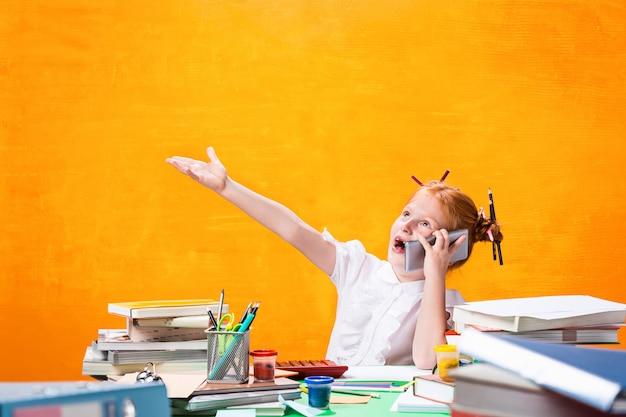 Rudowłosa nastolatka z dużą ilością książek w domu.