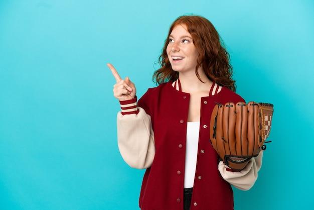 Rudowłosa nastolatka z rękawicą baseballową odizolowana na niebieskim tle, która zamierza zrealizować rozwiązanie, podnosząc palec w górę
