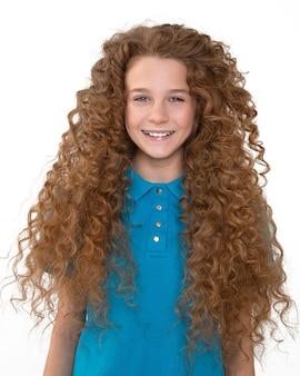 Rudowłosa piękna nastolatka z szelkami na białe zęby uśmiecha się szeroko patrzeć w kamerę na tle