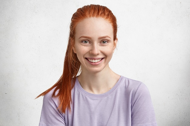 Rudowłosa piękna, zachwycona modelka jest w świetnym nastroju po udanym dniu, ma piegowatą skórę i rudy kucyk, pozuje na białym betonie