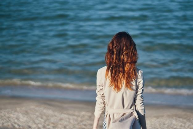 Rudowłosa podróżniczka w płaszczu i koszulce na plaży nad morzem letnie wakacje