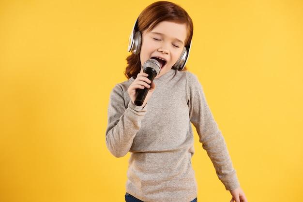 Rudowłosa radosna dziewczyna w słuchawkach śpiewa karaoke.