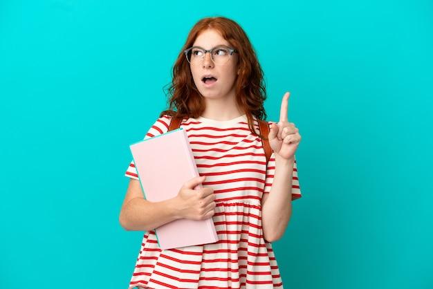Rudowłosa studentka nastolatka odizolowana na niebieskim tle myśląca o pomyśle wskazującym palec w górę