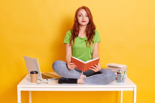 Rudowłosa studentka siedzi na stole ze skrzyżowanymi nogami, trzymając książkę w dłoniach, patrzy na kamerę, jest zmęczona nauką na odległość, ubrana na co dzień.