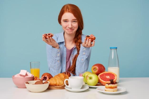 Rudowłosa szczęśliwa śmieszna kobieta je śniadanie
