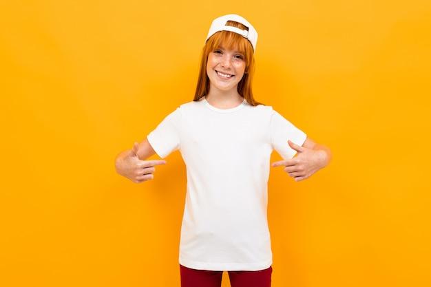 Rudowłosa urocza dziewczyna w białej koszulce na pomarańczowej ścianie, wskazuje palcami na siebie, makietą