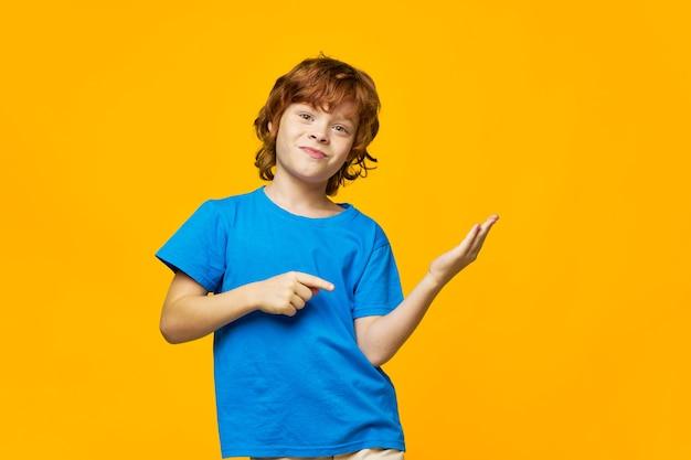 Rudowłose dziecko pieści i pokazuje ręce na bok