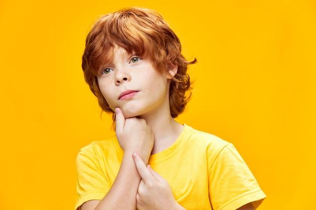 Rudowłose dziecko trzyma ręce w pobliżu twarzy wygląda z boku zbliżenie przycięty widok żółta ściana na białym tle