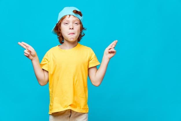 Rudowłosy chłopak grymasuje, wskazując rękami w różnych kierunkach na niebieskim tle
