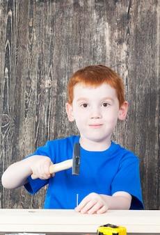 Rudowłosy chłopak o europejskim wyglądzie w konstrukcji drewnianej, w ręku trzyma młotek i gwoździe