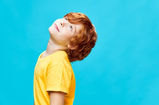 Rudowłosy chłopak patrząc żółtą koszulkę na niebieskim tle na białym tle