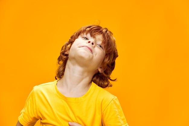 Rudowłosy chłopak w żółtej koszulce odchylił głowę do tyłu na odosobnionym tle