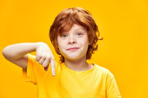 Rudowłosy chłopak w żółtej koszulce uśmiech i wskazuje w dół