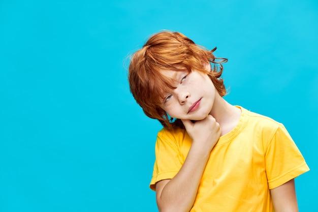 Rudowłosy chłopak z głupim wyrazem patrzy w bok i trzyma rękę przy twarzy