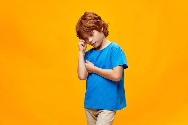 Rudowłosy chłopiec pochylił głowę ze smutnym wyrazem twarzy na żółtym tle