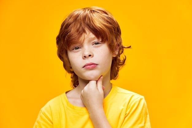 Rudowłosy chłopiec podejrzany wygląd na brodę zbliżenie studio żółty t-shirt prowadził tło