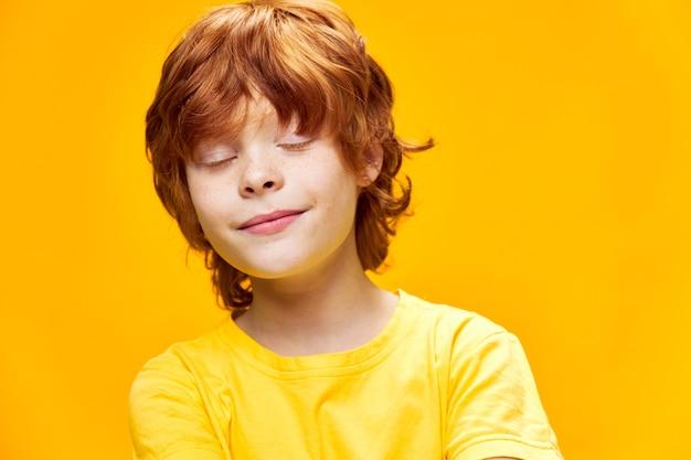 Rudowłosy chłopiec twarz z bliska zamknięte oczy uśmiech żółta koszulka