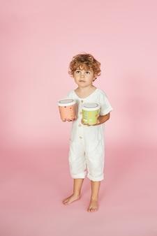 Rudowłosy chłopiec w kolorowych papierowych pudełkach. opakowania jednorazowe i koncepcja eko