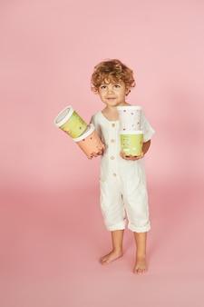 Rudowłosy chłopiec w kolorowych papierowych pudełkach