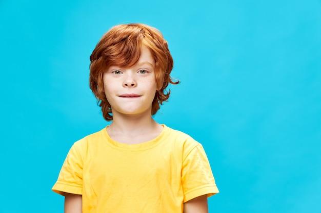 Rudowłosy chłopiec z bliska przygryzł wargę żółtej koszulki