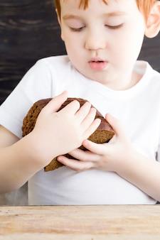 Rudowłosy chłopiec z bochenkiem chleba i nożem, zbliżenie pracy w kuchni podczas gotowania