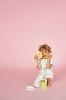 Rudowłosy chłopiec z kolorowymi papierowymi pudełkami z wiórkami owocowymi