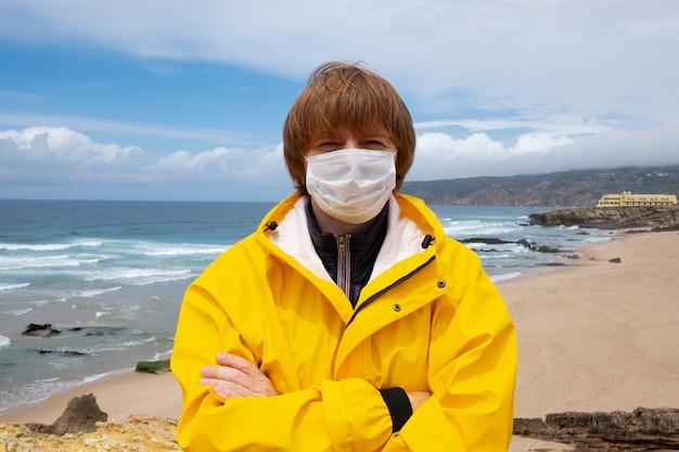 Rudowłosy facet ubrany w maskę i żółty płaszcz przeciwdeszczowy