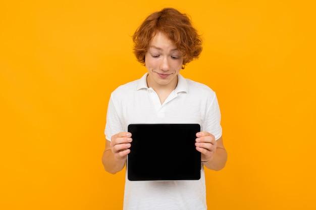 Rudowłosy facet w białej koszulce pokazuje wyświetlacz tabletu z makietą na żółtym tle