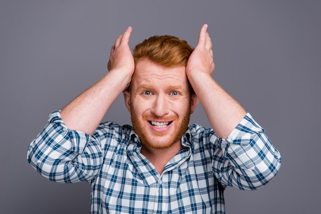 Rudowłosy facet w niebieskiej koszuli w kratkę pozujący przy szarej ścianie