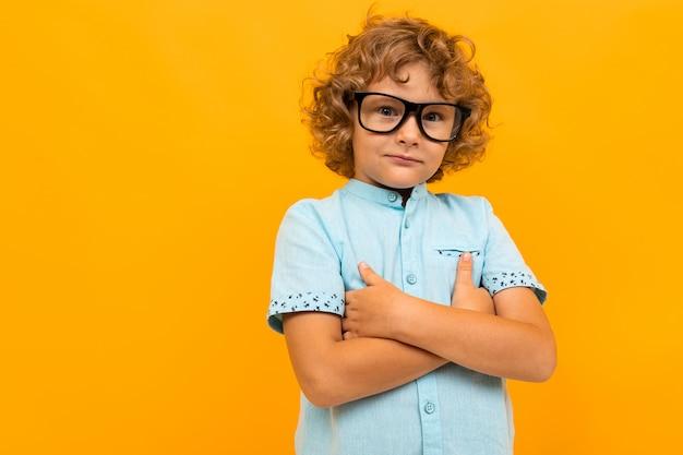 Rudowłosy kędzierzawy chłopiec w okularach i jasnoniebieski t-shirt skrzyżowali ręce na żółtym