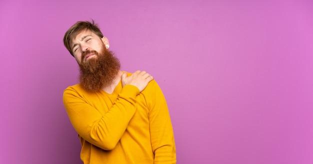 Rudowłosy mężczyzna z długą brodą na fioletowej ścianie cierpiący na ból w ramieniu za to, że podjął trud